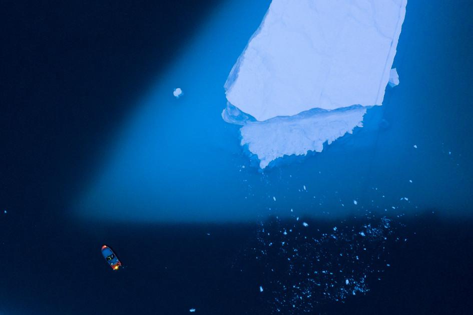 Исследовательская лодка приближается к айсбергу у восточного побережья Гренландии