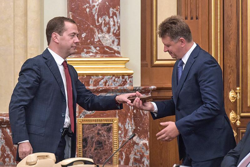 Премьер-министр РФ Дмитрий Медведев (слева) во время поздравления министра транспорта Максима Соколова (в центре) с днем рождения на заседании правительства России