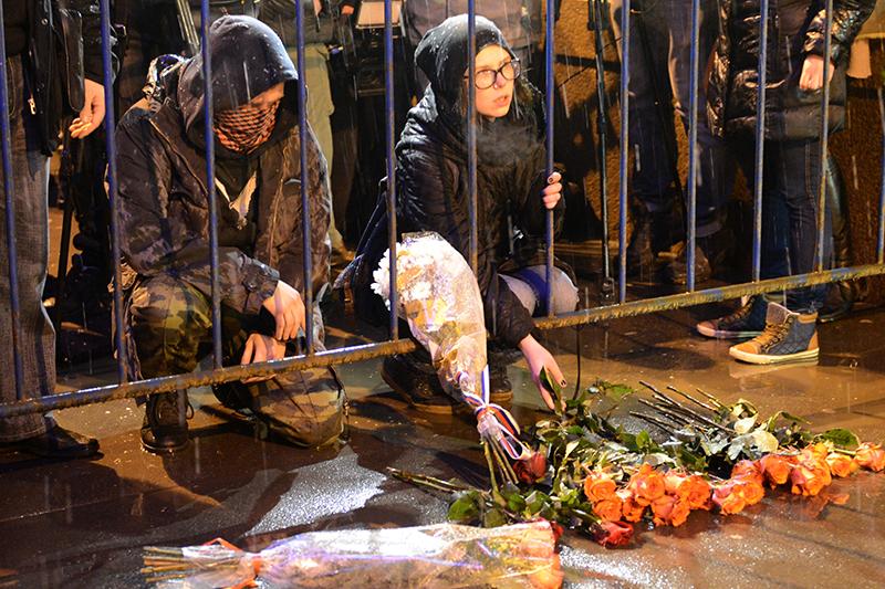 Люди несут цветы к месту убийства политика Бориса Немцова, который был застрелен на Большом Москворецком мосту
