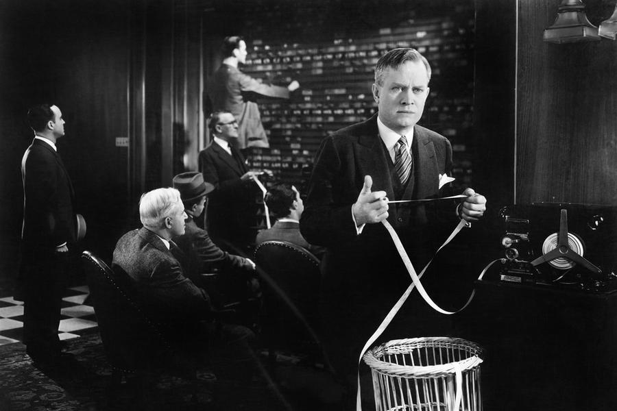 Мужчина в брокерском офисе держит в руках тикерную ленту с котировками акций