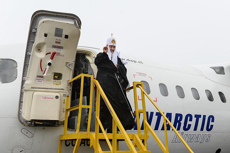 Патриарх спускается по трапу самолета Antarctic Airways