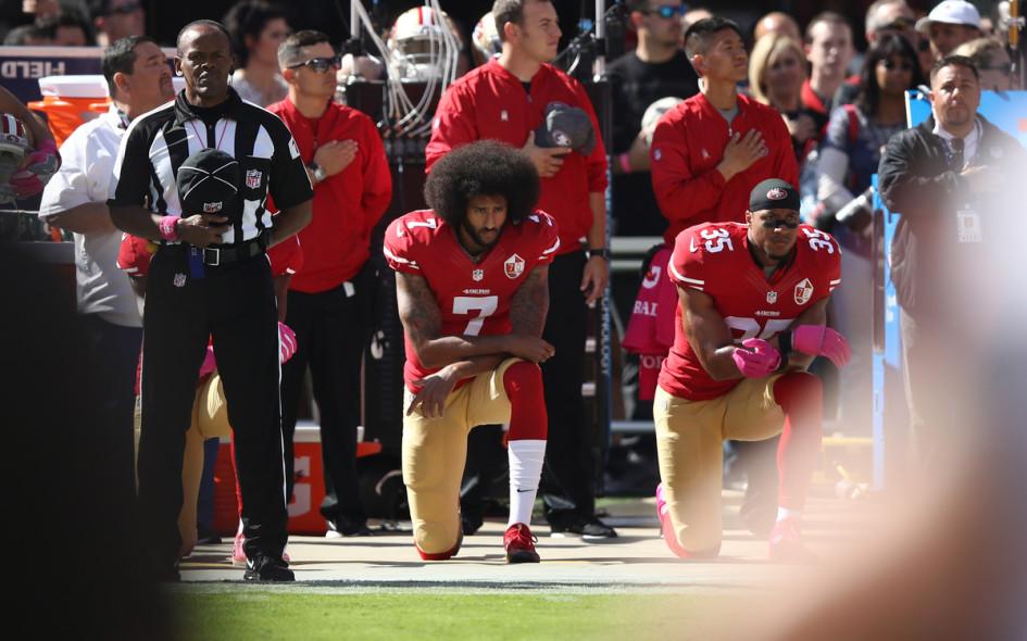 Колин Каперник (#7) преклоняет колено во время исполнения американского гимна перед матчем Национальной футбольной лиги в октябре 2016 года.