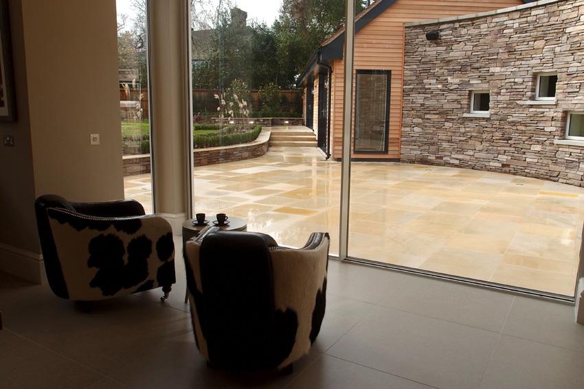Нажатием кнопки стеклянные двери полностью открываются, предоставляя проход на заднюю террасу и в сады