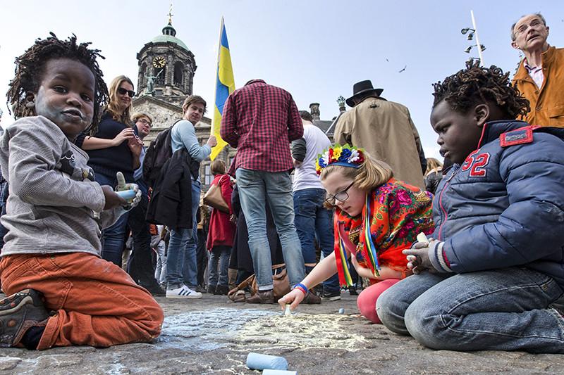 Дети рисуют флаг Украины на площади Дам в Амстердаме в преддверии референдума о соглашении об ассоциации. 3 апреля 2016 года