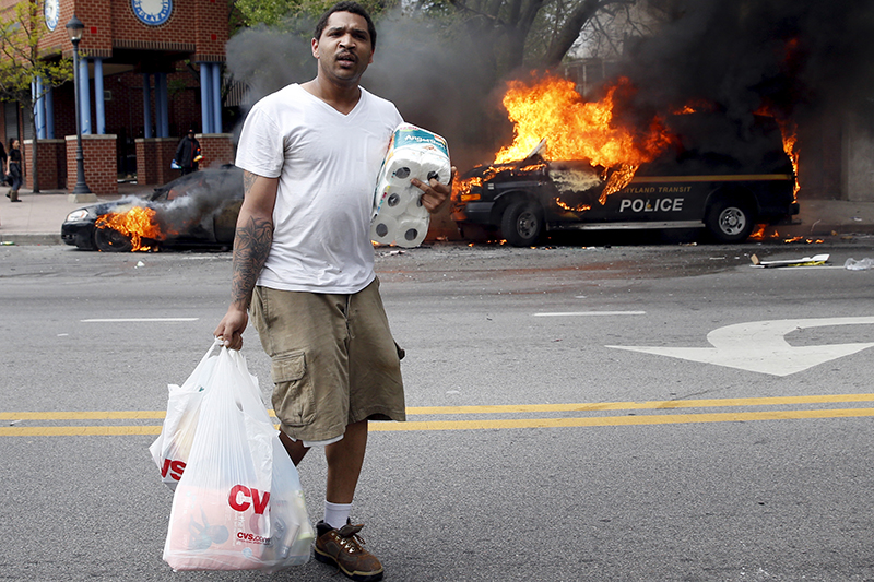 Человек с похищенными в магазине товарами проходит мимо горящих машин во время столкновений в Балтиморе