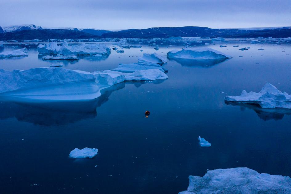 Лодка маневрирует между айсбергами