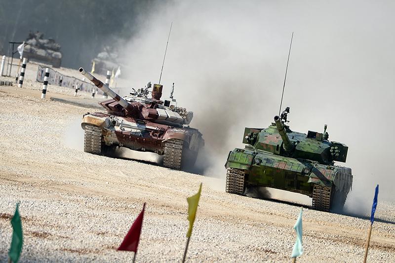 Экипаж из Китая на танке «Тип-96А» (справа) и экипаж из России на танке Т-72Б на соревнованиях чемпионата мира «Танковый биатлон 2014» на полигоне 2-й гвардейской мотострелковой Таманской дивизии в поселке Алабино
