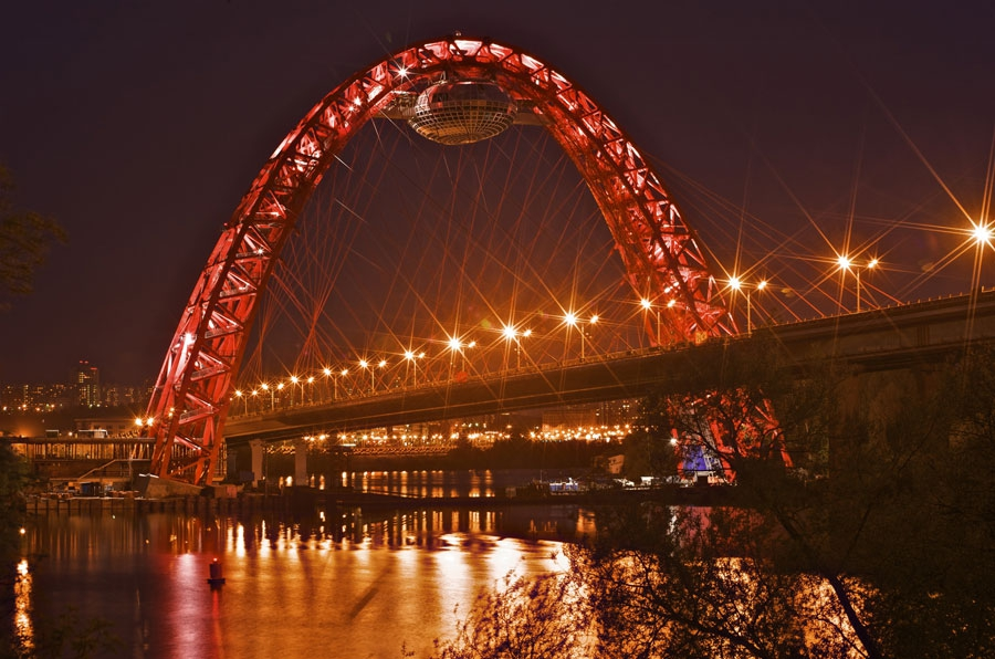 """Живописный мост с футуристической, похожей на диско-шар или летающую тарелку смотровой площадкой, был построен еще в 2007 году. В импровизированной """"капсуле"""" планировали открыть ресторан, кафе со смотровой площадкой, однако сложности с доставкой продуктов наверх и строгий запрет на ее приготовление делали эти проекты практически нереализуемыми. Однако весной 2012 года правительство Москвы выделило 650 млн рублей на обустройство Дворца бракосочетания и еще 150 млн на расположенную по соседству Аллею влюбленных - романтичных дорог, тропинок, около которых молодожены смогут посадить свое дерево"""