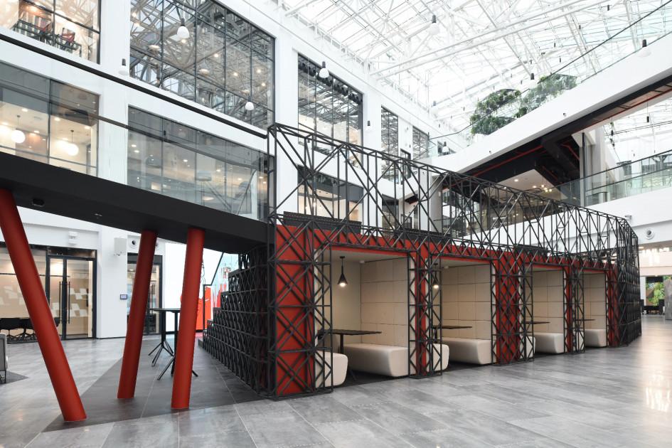 Изолированные переговорные кабинки для работы и взаимодействия с коллегами в атриуме офиса.