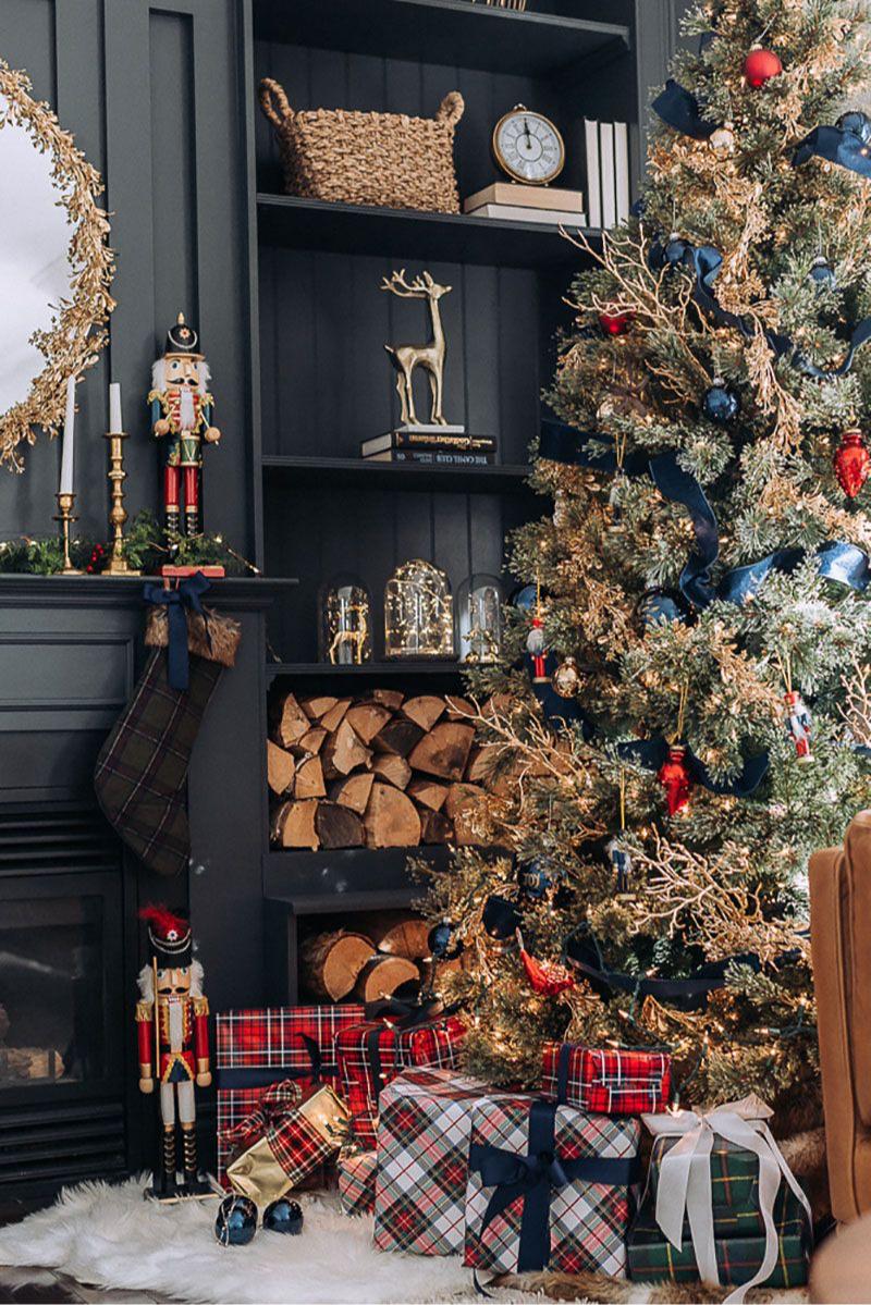 Украшение камина с помощью новогоднего носка, подсвечников, композиции из веток и игрушки. Елка, украшенная игрушками с подарками