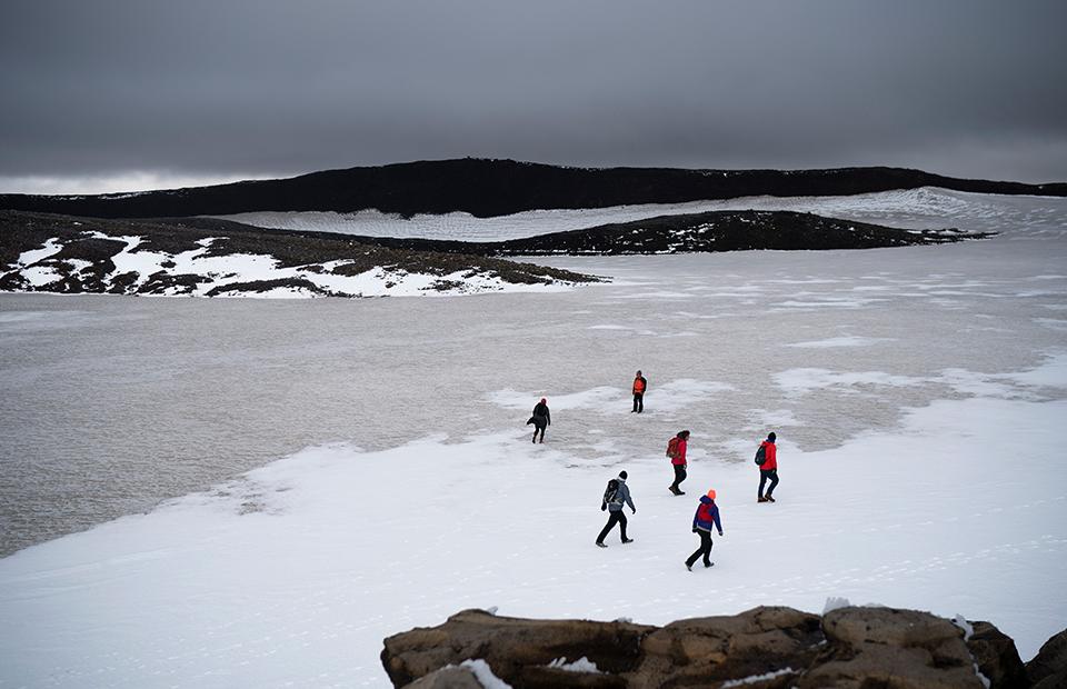 Исландские официальные лица и активисты идут по заснеженному кратеру вулкана в том месте, где раньше был ледник Окйокуль. 18 августа 2019 года