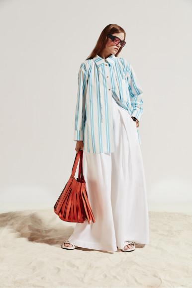 Рубашка Rejina Pyo, брюки Brunello Cucinelli, сумка Valentino Garavani, браслет Paco Rabanne, очки и шлепанцы— все Balenciaga