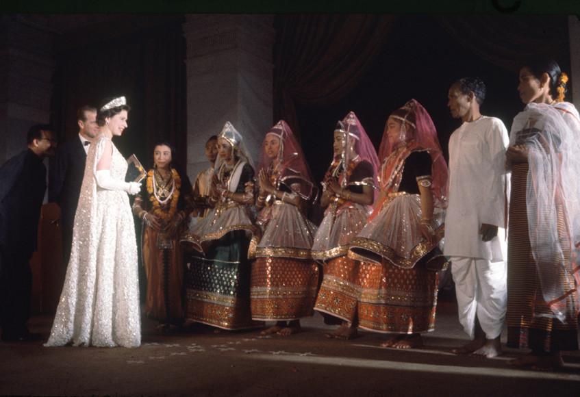 Елизавете II выбрала белое кружевное платье авторства Нормана Хартнелла с изображением цветов лотоса и сотнями жемчужин
