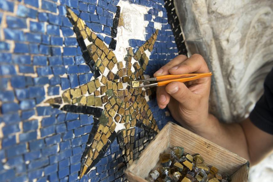 Процесс реставрации синей мозаики с золотыми звездами на фасаде базилики Святого Марка в Венеции