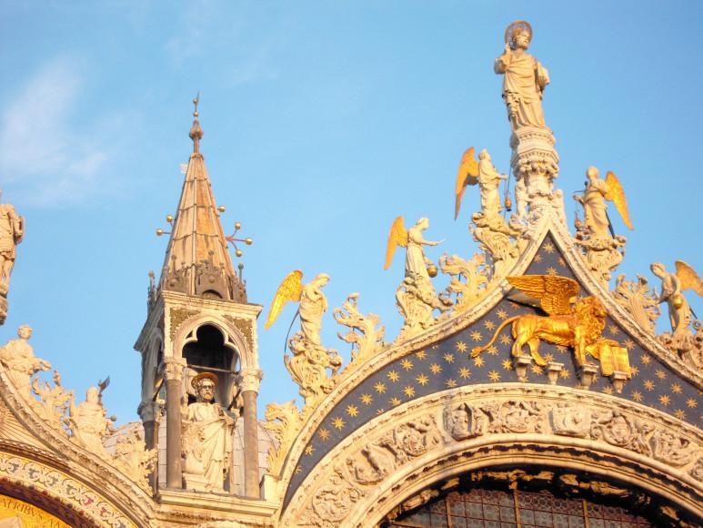 Отреставрированная скульптура крылатого льва Святого Марка и синяя мозаика с золотыми звездами на фасаде базилики Святого Марка в Венеции